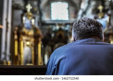 An unidentified man praying in a church.