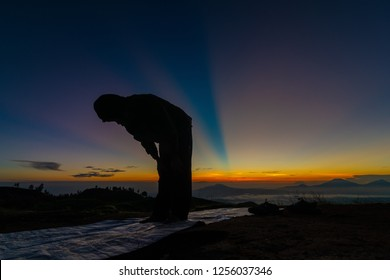 Unidentified man prays during sunrise on top of a mountain in Indonesia.
