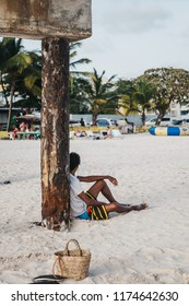 Unidentified man relaxing, sitting on the white sands of Carlisle Bay beach in Bridgetown, Barbados.