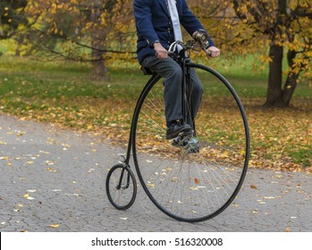 An unidentified man riding a penny-farthing bicycle in a park with fallen autumn leaves