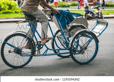 Unidentified man riding a traditional cyclo in Saigon Notre-Dame Cathedral Basilica, Vietnam.