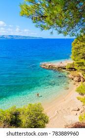 Unidentified man standing in water near famous Zlatni Rat beach in Bol town, Brac island, Croatia