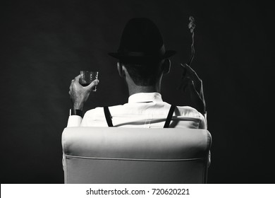 an unidentified man in a suit and hat with a cigar and whiskey staring into the distance. View from the back. The man is a mafia. Millionaire gangster businessman boss