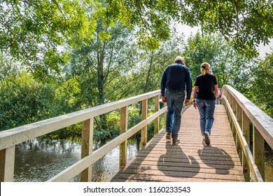 An unidentified  man and woman in casual clothes and shoes walk over a simple wooden bridge over a narrow river on a sunny day in the Dutch summer season.
