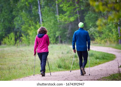 Unidentified Man and woman walking in a natural park using trekking poles
