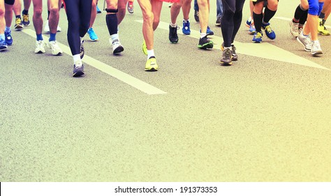 Unidentified marathon athletes competing in fitness and healthy active lifestyle feet on road