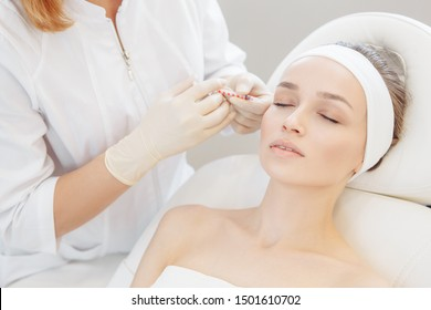 Unidentified master cosmetologist makes botox injections into the eyebrow of a beautiful young woman client. The concept of rejuvenating aesthetic procedures