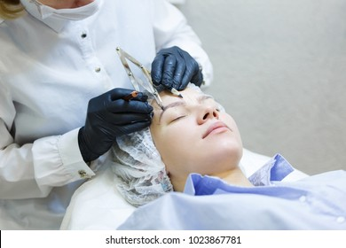 Unidentified master in gloves and in robe measures the proportions of eyebrows with special instrument and holds pencil. Concept of microblading
