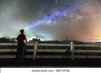 Unidentified men with torch light over the head  and beautiful milkyway in the middle  of night at Muadzam Shah, Malaysia(Visible noise due to high ISO,soft focus, shallow DOF, slight motion blur)