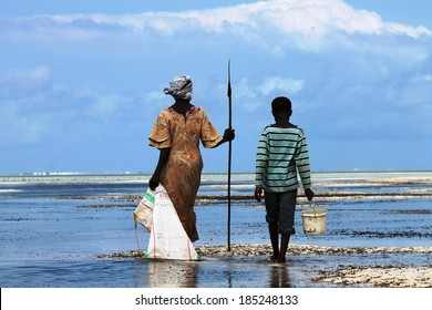 Unidentified mother carrying a spear and her young son off to collect marine food in the Zanzibar Lagoon