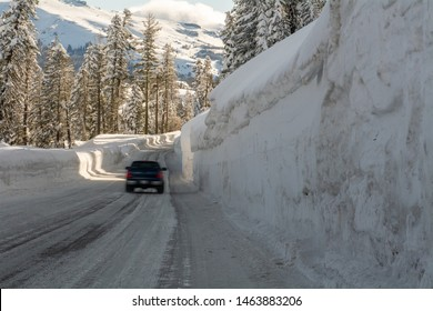 Unidentified moving vehicle on mountain road highway 88 towards Carson Pass, California, USA, on a winters day featuring five feet of snow on the side of the road after several storms.
