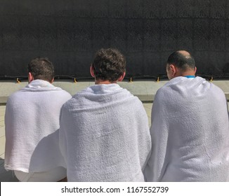 Unidentified Muslim pilgrims in white ihram cloth face the Kaabah waiting for a prayer time in Mecca, Saudi Arabia.