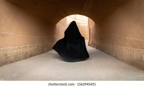 Unidentified muslim woman, dressed in black hijab walks on the narrow street of old city Yazd in Iran.