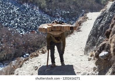 An unidentified Nepalese porter carrying a heavy load to the pass in Sagarmatha National Park, Himalayas
