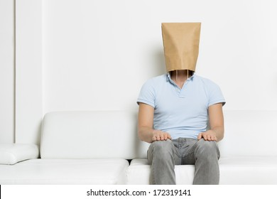 Unidentified neutral man with head covered by a brown paper bag sitting on sofa, empty space for text, on white background.