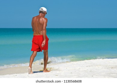 Unidentified Older Man walking on the beach getting exercise and enjoying a beautiful sunny day.