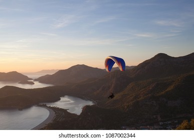 An unidentified paraglider flying at sunset over Blue lagoon in Oludeniz, Turkey