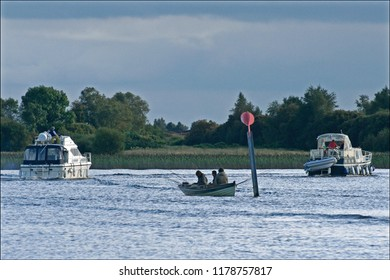 Unidentified people fishing, and pleasure craft at early morning on the Shannon River, in Athlone, Ireland