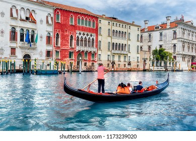 Unidentified people on a traditional Gondola with scenic architecture along the Grand Canal in Cannaregio district of Venice, Italy