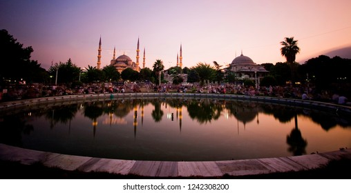 Unidentified people sitting and eating iftar in ramadan. The Sultanahmet Mosque the Blue Mosque view from the Sultan Ahmed Park and fountain in Istanbul, Turkey.