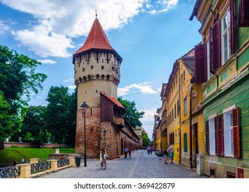 Unidentified people wander along the medieval defense wall and The Carpenters' Tower in Sibiu city, Transylvania region, Romania.