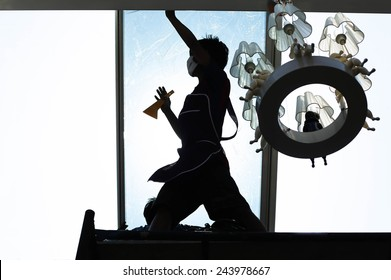 unidentified  people wrappers tinting a glass house window with a tinted foil in silhouette