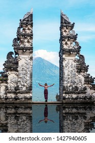 Unidentified person at the gate of Pura Penataran Lempuyang infront of Mt Agung Volcano in Bali Indonesia.