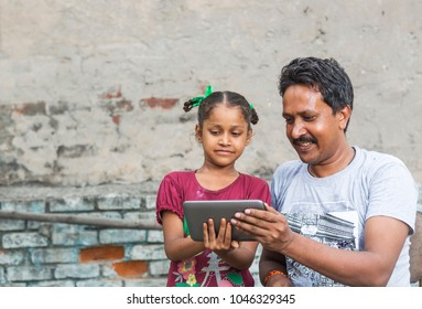 an unidentified person helps an unidentified child in her study on digital tablet in ludhiana, punjab, india on 15 august 2017