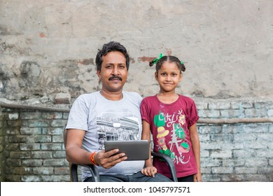 unidentified person in ludhiana, punjab, india, helping his unidentified daughter in study through digital tablet on 15 august 2017