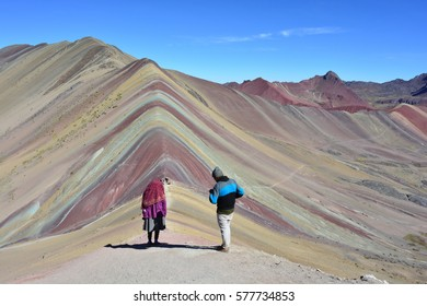 Unidentified peruvian couple with typical clothes hiking the Vinicunca Mountain, also known as Cerro Colorado or Rainbow Mountain, in Cusco, Peru