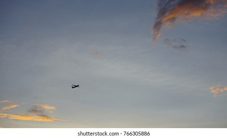 Unidentified plane flying through a blue sky and golden hour clouds, sunset.