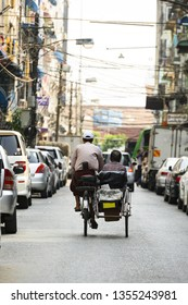 A unidentified Sai Kaa driver is carrying a passenger on his side car among the narrow streets of Yangon, Myanmar. The Sai Kaa rickshaw is a type of tricycle designed to carry passengers used in Asia