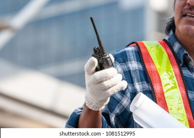 Unidentified senior Asian civil engineer wearing white glove holding walkie talkie radio and blueprint command team to solving problem on construction area, work with team work to finished the project