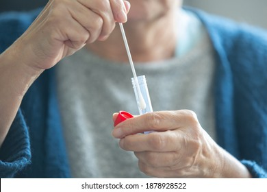 Unidentified senior woman performing a swab test for coronavirus covid-19 and preparing a package for laboratory testing.