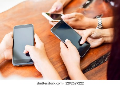 Unidentified three young people using  smartphone together. In selective focus.Close-up. Technology gadget and phone addiction concept.