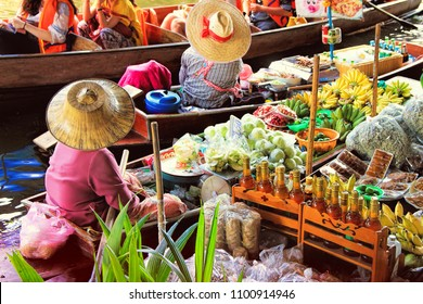 unidentified tourists and traditional vendors on the famous floating market Damnoen Saduak in Bangkok. It is a traditional market on the chanels , where they sell goods and food from the boats.