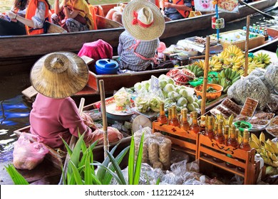 unidentified tourists and traditional vendors on the famous floating market Damnoen Saduak in Bangkok. It is a traditional market on the khlongs, where they sell goods and food from the boats.