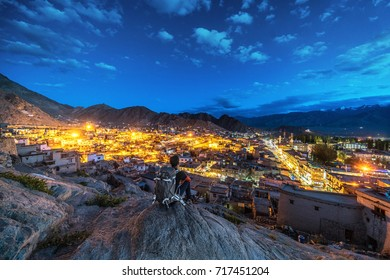 Unidentified traveler enjoying dusk view of Leh City from Leh Palace. eh, a high-desert city in the Himalayas, is the capital of the Leh region in northern India's Jammu and Kashmir state.
