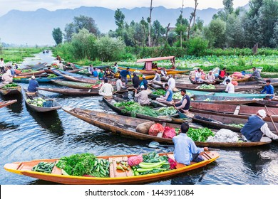 Unidentified vegetable vendors sell their produce on their boat  at floating vegetable market - Dal Lake, Sri Nagar, India on June 26, 2018