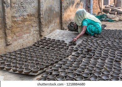 unidentified woman collecting diyas -earthen pots  on 31 October 2018 in ludhiana, punjab, india