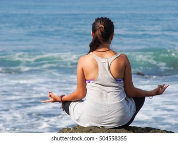 unidentified woman doing yoga on the beach to relax her body and soul