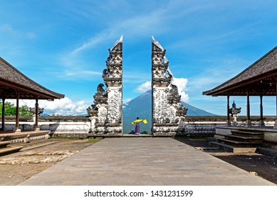 Unidentified Woman at Gate at Pura Lempuyang Luhur with Mr Agung Volcanic View, sacred Hinduism temple in Bali Indonesia.