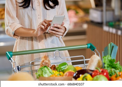 An unidentified woman holding smart phone standing next to basket full of vegetables and  healthy super food while shopping in the supermarket