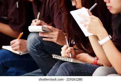 unidentified young asian female student school girls wearing jeans sitting on the floor outdoor taking note at site visit on small paper notebook with pen and pencil