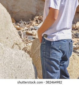 An unidentified young Asian man in casual dress is urinating in the rocks beach at natural bay. Urinating in public places is popular in Vietnam.