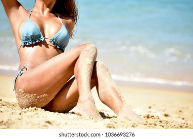 Unidentified young attractive sexy and healthy tan skin woman Model sitting on soft sand beach for sunbath wearing cute light blue  two-pieces swimsuit relaxing by the sea background on vacation.