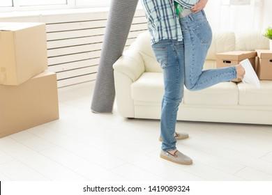 Unidentified young couple in denim pants embracing rejoicing in their new apartment during the move. The concept of housewarming and credit for new housing.