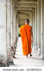 Unidentified young novice monk walks at one of the ruined temple in Angkor Wat.