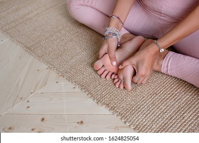 An unidentified young slim woman in a pink suit is doing a foot massage and sitting in the lotus position. Young woman yoga teacher does an advanced lotus position during yoga class
