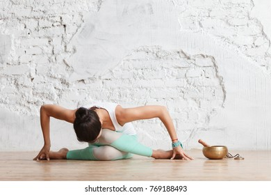 Unidentified young woman in gymnastic costume makes an exercise from yoga in the gym next to copper cup and pestle. Space for text
